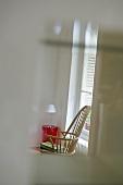 Blick durch Fensterausschnitt auf Sprossenrückenlehne eines Holzstuhls mit rotem Kunststoff- Beistelltisch