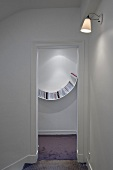 A view through an open door onto a curved bookshelf on a white wall