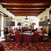 A living room with a rustic wood beam ceiling in a South African country house with a red sofa and table lamps with striped shades