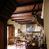 A dining room in a South African country house - an antique dining table, a wood beam ceiling and a stuffed animal head on the wall