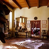 Eingangshalle im südafrikanischen Haus mit Zebrafell auf Terrakottaboden und offener Durchgang zum Wohnraum