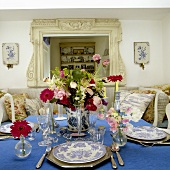 A table laid with silver cutlery, flowers and a blue tablecloth