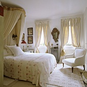 A double bed with a canopy and an antique armchair in a white bedroom