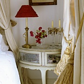 A bedside lamp with a red shade and a glass candlestick on a Rococo-style table