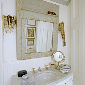 A marble-topped washstand and a vintage mirror with a grey frame in the corner of a bathroom