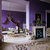 A fireplace room with an open doorway into a living room with purple wallpaper with a gold pattern
