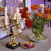 Red flowers in a glass vase and a gilded candle stick next to a mocca cup on a wooden shelf