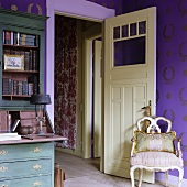 An antique Rococo-style chair in front of an open door with a view into a hallway