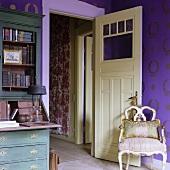 Antiker Stuhl im Rokokostil vor offener Zimmertür und Blick in Flur