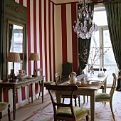 Coffee break in a dining room with a red and white striped wall and green curtains on a balcony door