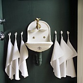 An old sink with white towels hung on the dark grey wall