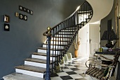 A flight of stairs with a dark grey wall and a black and white tiled floor in the hallway of a country house