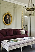 An upholstered Rococo-style coffee table with a purple two seater and a picture hanging on the wood panelled wall