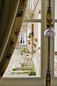 A view through a window of a brick facade of a country house