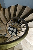 Stairwell of a spiral staircase drawing your attention down below to a checkerboard floor