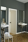 Clean lines in a bathroom - wash basins with mirrors and vertical strip lighting on a grey wall either side of the door