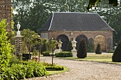 A gravel driveway leading to a country house with a view of the front garden with pedestals and a side house with rounded archways