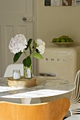 White flowers in a vase on a dining table with marble tabletop