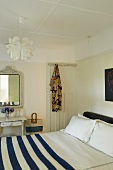 Double bed with a blue and white bedspread in a bed room (country style decor)