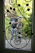 A view of a child through a window featuring floral metalwork