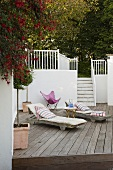 Loungers on a wooden terrace with a flight of white stairs leading to a garden