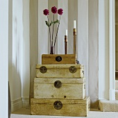 Blumenvase und Kerzenhalter auf antikem Truhenstapel vor gestreifter Wand