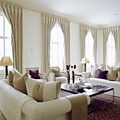 weiße Sofagarnitur und Fenster mit bodenlangen Vorhängen im eleganten Wohnraum