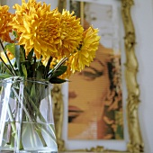 Yellow flowers in a glass vase and a portrait of a woman on the wall