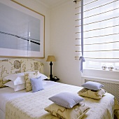 Stacks of cushions on a bed and a white blind at the window