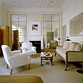 Covered armchairs, an antique three-seater sofa and a side table with a fur cover in an English living room