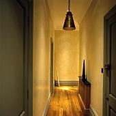 An illuminated hallway with grey door and a narrow wooden shelf