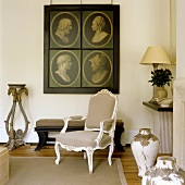 A Rococo armchair in front of portraits with dark backgrounds