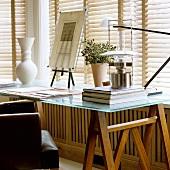 Arbeitstisch mit Glasplatte auf Holzböcken vor geschlossener Jalousie am Fenster
