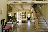 An entrance hall with a natural stone floor and a flight of stairs with a rustic wood beam ceiling