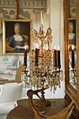 Burning candles in candle holders and a crystal chandelier