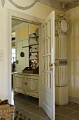 An antique grandfather clock standing next to an open door with a view of a plate rack in a dining room