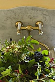 Freshly picked berries in a marble sink with brass taps