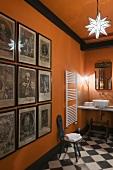 Ahnengalerie im knallorangen Badraum mit Schachbrettmuster auf dem Boden