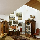 A collection of antique furniture and paintings in the attic of a house