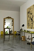 A minimalistic mixture of styles - an anteroom with a Baroque mirror and palatial furniture on the concrete floor