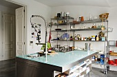Cool materials - a glass-topped, stainless steel kitchen counter in front of a wall shelf