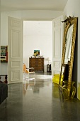An access room in a period building with a reflective concrete floor and a gold framed mirror leaning against the wall