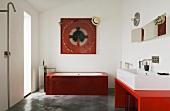 Minimalistisch designtes Bad - Waschbecken auf rotem Tisch und rote Glaswanne auf Betonboden