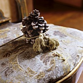 A pine cone tied with string on a worn chair