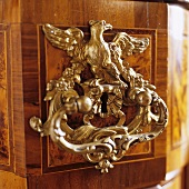 A handle and a lock on a piece of furniture with an animal figure