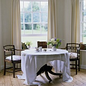 A dining table with dark wooden chairs in a bay window with a view of a garden