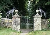 Two dogs standing on a weathered stone wall with a garden gate