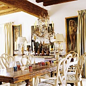 A rustic dining table with a chandelier hanging from the wood beam ceiling