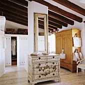A rustic attic room with a painted chest of drawers in the middle of the room