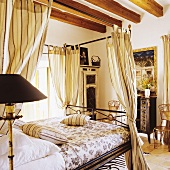 A delicate four poster bed under a rustic wood beam ceiling